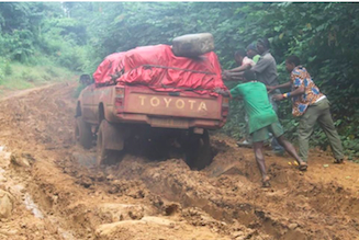 Four-wheel drive vehicle stuck in mud in Nguti/Cameroon as passengers push to rescue