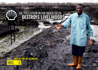 "Bodo campaign poster, the text says: ""Oil pollution in the Niger Delta destroys livelihoods"" ""Shell. Own up. Pay up. Clean up."" Image is of Pastor Christian Lekoya Kpandei showing the damage done to his fish farm in Bodo, Nigeria, May 2011. The farm flourished before the August 2008 oil spill, but the pollution destroyed his fish farm, leaving him and his workers without a regular income. Bodo, Nigeria, May 2011. (PHOTO: Amnesty International)"